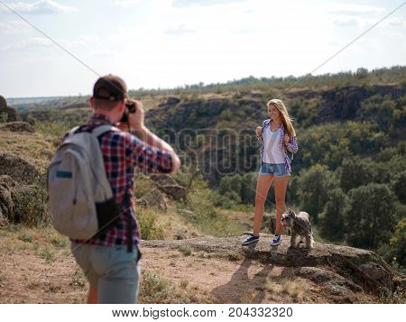 Image of boy, making picture of a girl at the natural view. Climbing the rock. Sport and active life concept.