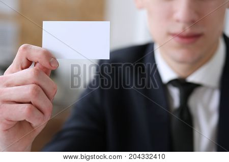 Smiling businessman in suit hold in hand blank calling card portrait. White collar partners company name exchange executive or ceo introducing at conference product consultant sales clerk concept