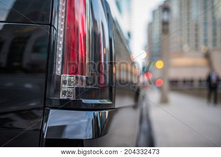 Stop light of a black SUV vehicle with blurred background