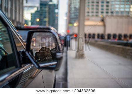 Reflection in the mirror of black SUV of city skyline