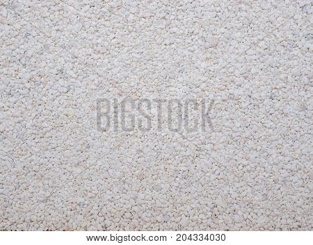 Small grey beige white stones close-up texture, summer, beach concept. Stone for mixed cement flooring gardens. Picture of variation of gravel lying on a road.