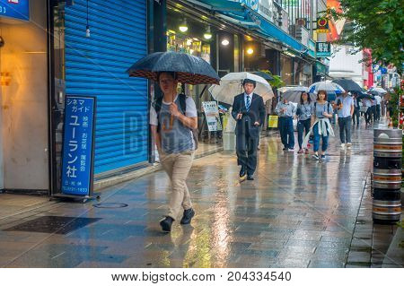 TOKYO, JAPAN JUNE 28 - 2017: Unidentified people walking under the rain in the sidewalk with umbrellas in Jimbocho district located in Tokyo, Japan.