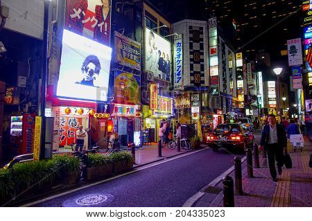 TOKYO, JAPAN JUNE 28 - 2017: Crowd of people walking and enjoying the beautiful famous Kabukicho red lights district, surrounding of big buildings and advertisements, located in Tokyo, Japan.