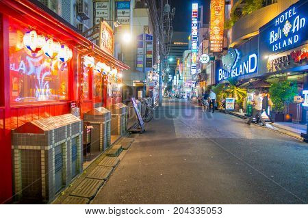 TOKYO, JAPAN JUNE 28 - 2017: Unidentified people walking at beautiful famous Kabukicho red lights district, surrounding of big buildings and advertisements, located in the city of Tokyo, Japan.
