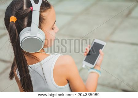 sweet child with headphones and white phone in hand, beatiful teenager listening to music in white headphones