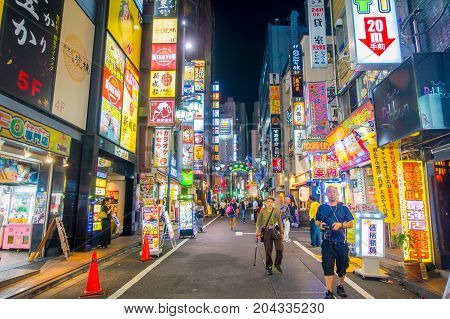 TOKYO, JAPAN JUNE 28 - 2017: Unidentified people walking and enjoying the beautiful famous Kabukicho red lights district, surrounding of big buildings and advertisements, located in Tokyo, Japan.
