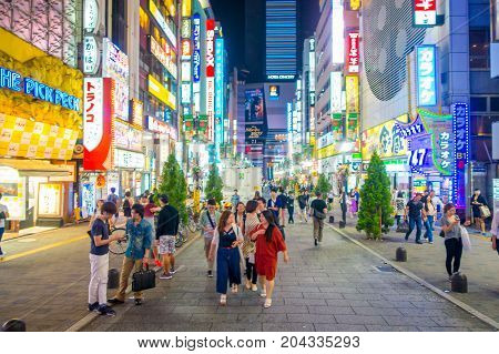 TOKYO, JAPAN JUNE 28 - 2017: Unidentified people walking at beautiful famous Kabukicho red lights district, surrounding of big buildings and advertisements, located in Tokyo, Japan.