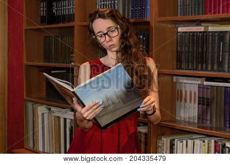 Funny Girl Reading a Book in front of a Bookshelf, Studying Woman in Glass