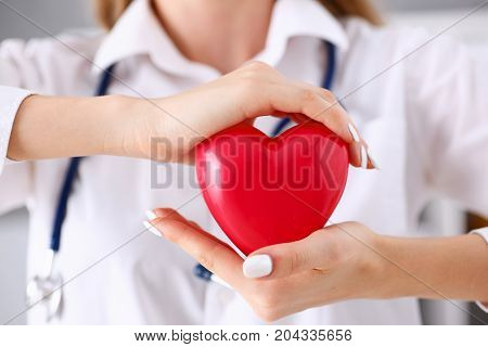 Female Doctor Hold In Arms And Cover Red Heart