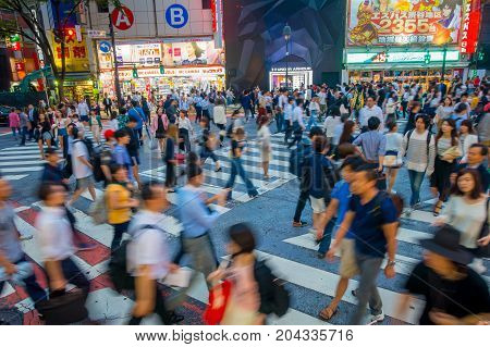 TOKYO, JAPAN JUNE 28 - 2017: Unidentified people crossing the Shibuya street in Tokyo, Japan. The famous scramble crosswalk is used by over 2.5 million people daily.