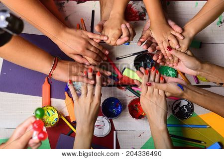 Creativity and art concept. Art supplies in male and female hands on white wooden desk background top view. Artists hands with stationery and colored paper. Hands hold markers pencils and paints