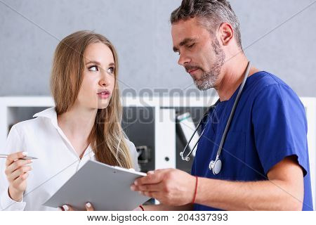 Handsome Mature Doctor Offer Pad To Sign With Silver Pen