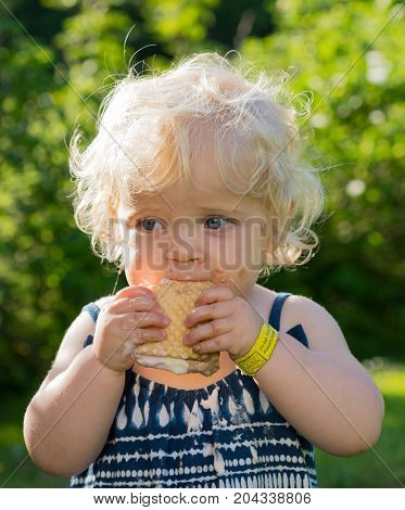 Blond girl eating a melting ice cream on holiday