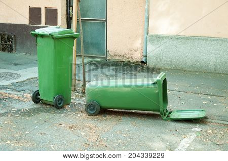 Two green plastic garbage can one is overturned lying on the street