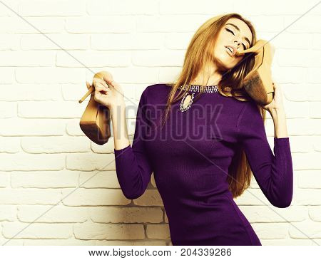 young fashionable sexy pretty woman or girl with beautiful long blonde hair on satisfied face in purple dress holding beige shoes or high heels near mouth on white brick wall background copy space