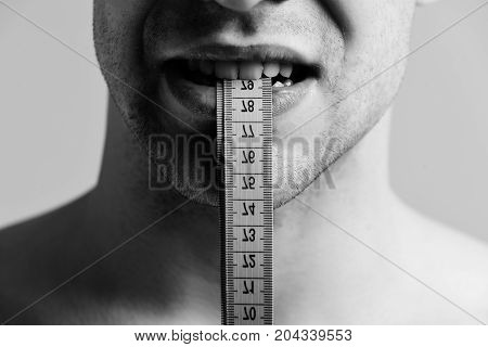 Weight Management Idea. Male Holds Blue Measuring Tape With Teeth