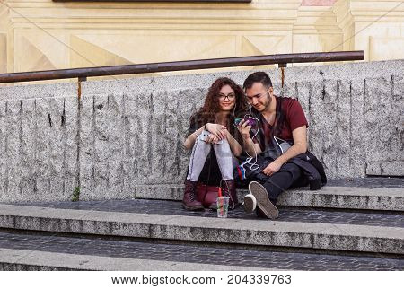 Milan , Italy 27 July 2017 : Couple listening to the music with earbuds from a smart phone with an urban background .