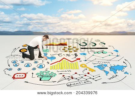 Businessman drawing abstract business sketch in desert. Sky with sunlight in the background. Success concept