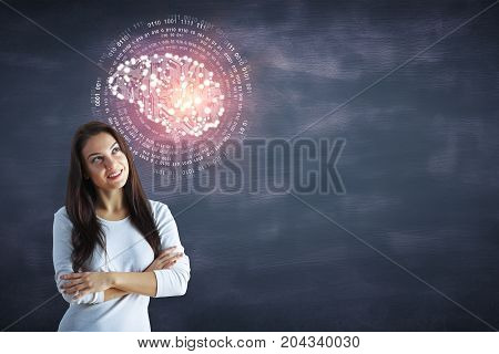Cheerful young woman with abstract circuit brain standing on chalkboard wall background with copy space. Artificial intelligence/ mind concept