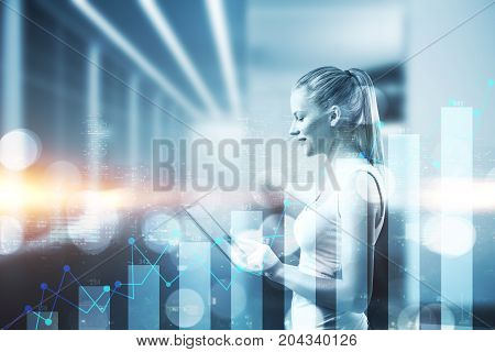 Side view of attractive woman using tablet on creative night city background with business chart. Technology and finance concept. Double exposure
