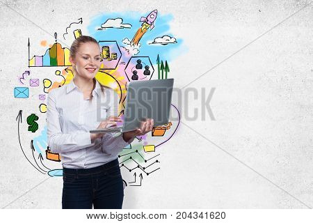 Smiling young businesswoman with laptop standing on concrete wall background with business sketch. Entrepreneurship concept