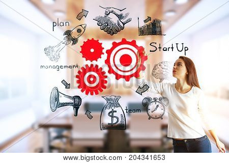 Thoughtful young woman drawing creative business sketch on blurry office interior background. Teamwork and targeting concept