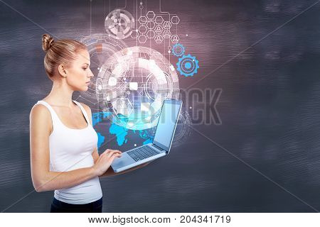 Thoughtful young woman using laptop with digital business hologram on chalkboard wall background. Innovation concept