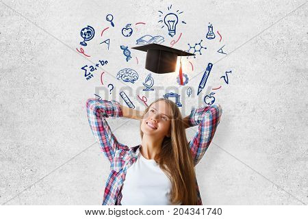 Cheerful young woman standing on concrete wall background with mortarboard and educational sketch. Knowledge concept