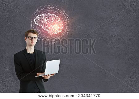 Thoughtful young businessman with laptop and abstract circuit brain standing on concrete wall background with copy space. Artificial intelligence/ mind concept