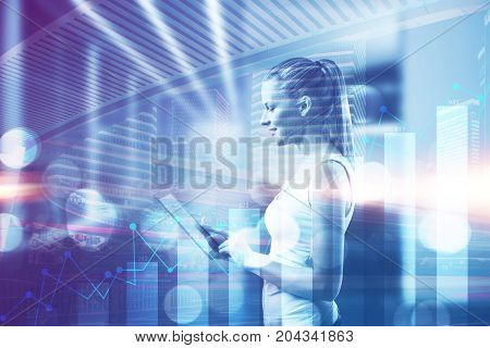 Side view of attractive woman using tablet on creative night city background with business chart. Technology and accounting concept. Double exposure