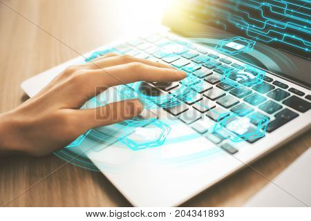 Side view and close up of female hand using laptop keyboard with abstract digital hologram. Technology and innovation concept