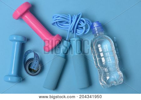 Jump Rope And Barbells Next To Bottle And Measure Tape
