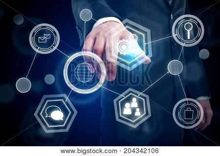 Businessman hand pointing at digtal business hologram on dark background. Innovation concept