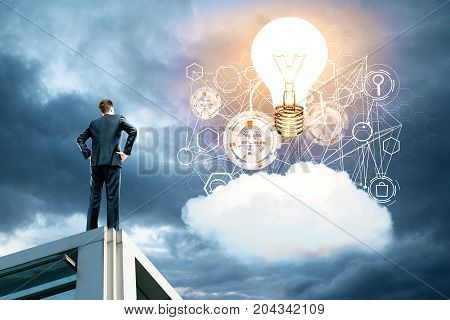 Back view of young businessman on rooftop looking at sky with cloud business hologram and glowing laptop. Innovation concept