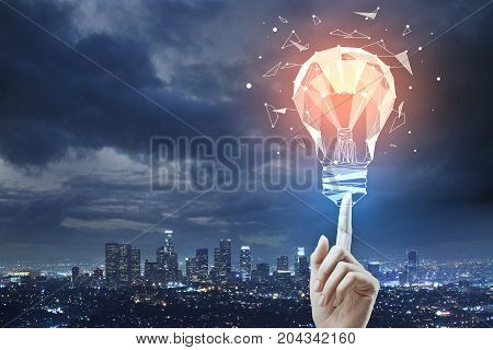 Female hand pointing at abstract polygonal lamp on night city background with cloudy sky and copy space. Innovation concept