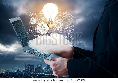Side view of young businessman using laptop with abstract cloud business hologram and glowing lamp on night city background. Innovation and analytics concept