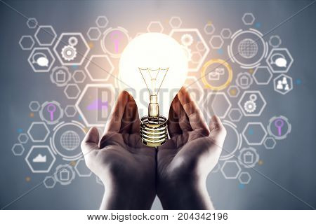 Female hands holding glowing lamp on abstract blurry background with business hologram. Idea concept