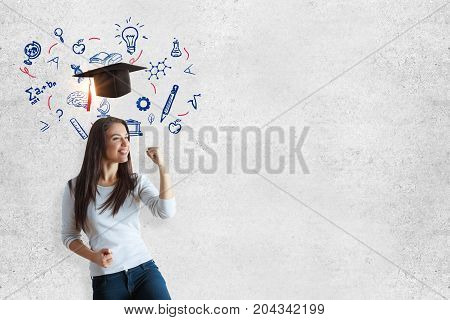 Cheerful young woman standing on concrete wall background with mortarboard and educational sketch. Education concept