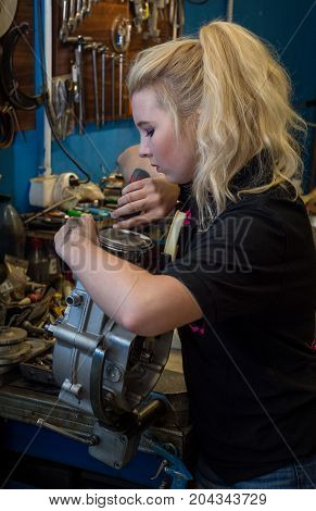 Breaking stereotypes - teenager girl working on broken motorcycle engine at mechanical workshop