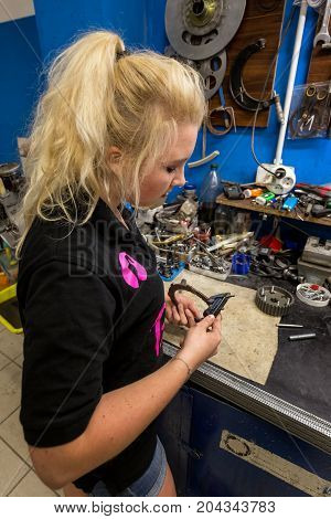Young blonde woman breaks stereotypes - working at mechanical workshop. Teenager girl using caliper to measure details dimensions