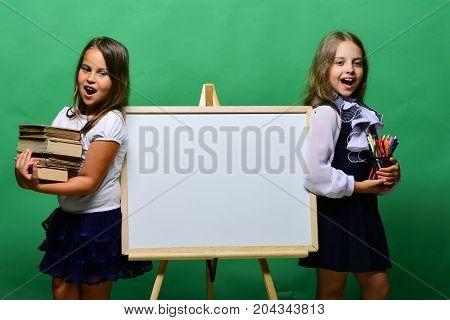 Schoolgirls Next To Whiteboard On Green Background
