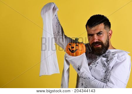 Halloween And Happy Holiday Concept. Guy With Beard Holds Pumpkin