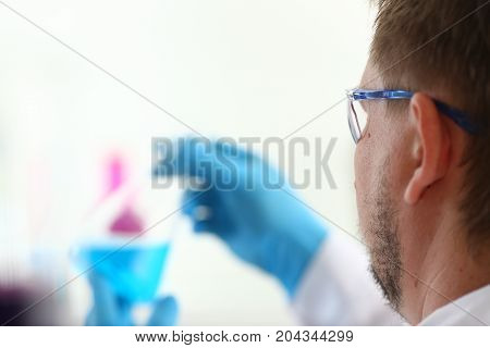 A Male Chemist Holds Test Tube Of Glass In His Hand Overflows