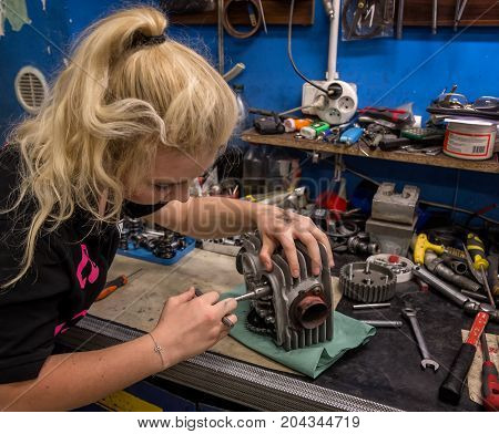 Breaking stereotypes - girl doing male job at mechanical workshop. Young woman repairs broken motorcycle engine