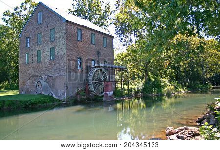 a green stream flows before an old brick gristmill