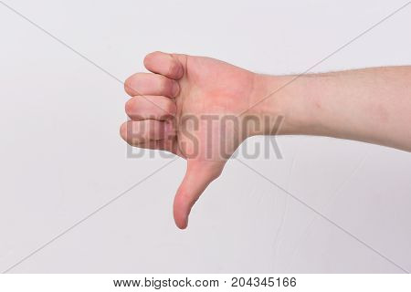 Male Hand Shows Thumbs Down Sign. Body Language Concept.