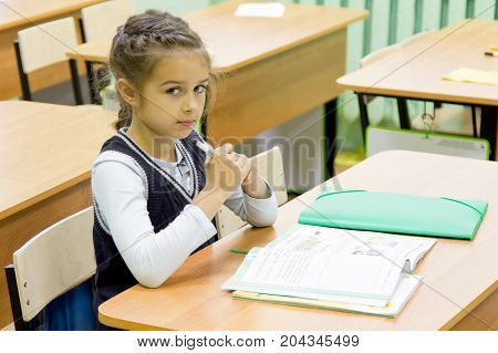 Back to school. Schoolgirl sitting at a desk indoors. Kid is learning in class