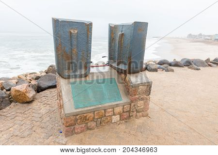 SWAKOPMUND NAMIBIA - JUNE 30 2017: A memorial plaque with pieces of the old jetty at the entrance to the historic jetty in Swakopmund in the Namib Desert on the Atlantic Coast of Namibia