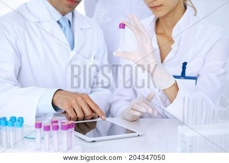 Team of  scientific researchers in laboratory studying substances or blood sample. New vaccine for pharmacology industry is s almost ready. Medicine and science concept.