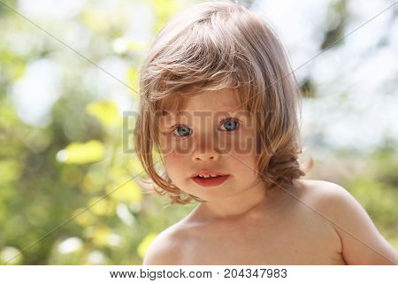 Happy Little Smiling Child On A Natural Background Walking In The Park